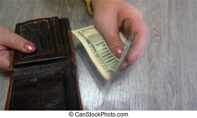 female hands hold dollar bills from her purse and puts them back into the purse