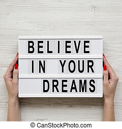 Female hands hold lightbox with text 'Believe in your dreams' over white wooden background. From above, overhead, flat lay.