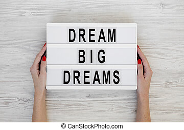 Female hands hold lightbox with text 'Dream big dreams' over white wooden surface, top view. Overhead, from above, flat lay.
