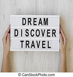 Female hands hold lightbox with text 'Dream Discover Travel' over white wooden background, overhead view. From above, flat lay, top view.