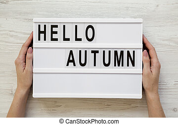 Female hands hold lightbox with text 'Hello Autumn' over white wooden background, top view. Overhead, flat lay, from above.