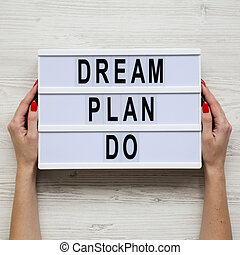 Female hands hold modern board with text 'Dream plan do' over white wooden background, top view. From above, flat lay, overhead.