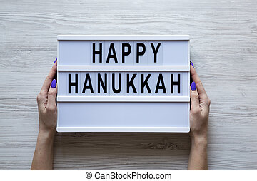 Female hands hold modern board with text 'Happy Hanukkah' over white wooden background, overhead view. From above, flat lay, top view.