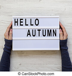 Female hands hold modern board with text 'Hello Autumn' over white wooden background, overhead view. Flat lay, from above.
