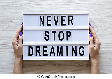 Female hands hold modern board with text 'Never stop dreaming' over white wooden background, overhead. Top view, from above, flat lay.