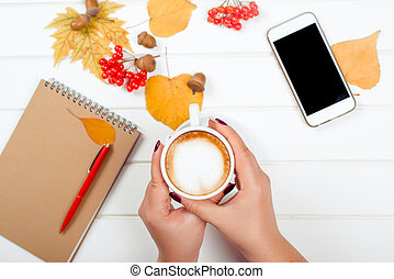 Female hands holding a cup of cappuccino. Autumn background, notebook with red pen, mobile phone on wooden table.