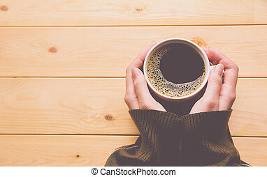 Female hands holding a cup of coffee over wooden table.
