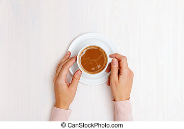 Female hands holding a cup of coffee with milk on a white wooden