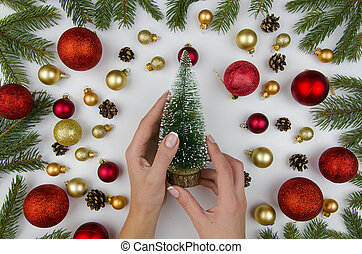 Female hands holding a decorative christmas tree. Christmas composition made of gold and red balls for a Christmas tree, and fir branches. Winter flat lay.