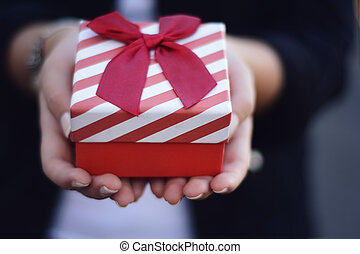 Female hands holding a gift box, present.