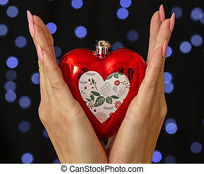 female hands holding a heart shaped Christmas toy