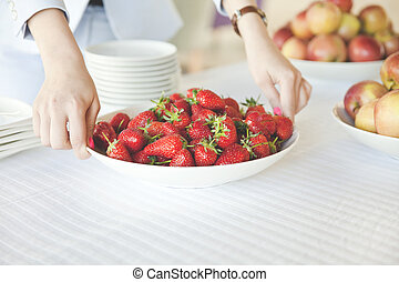 Female hands holding a plate full of strawberries