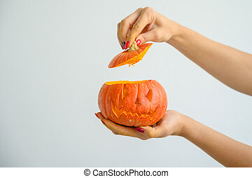 Female hands holding a pumpkin for Halloween. Close-up of a woman opens the jack-o'-lantern cover on a white background on the eve of all the saints. front view.