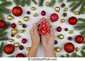 Female hands holding a red christmas tree toy.Christmas composition made of gold and red balls for a Christmas tree, cones and fir branches. Christmas background. Winter flat lay