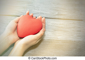 Female hands holding a red heart, the concept of love and care.