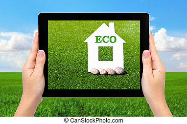 female hands holding a tablet computer with a house and an inscription on eco background of green grass and blue sky