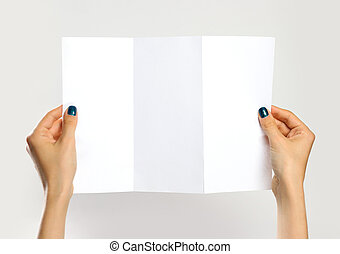 Female hands holding a white booklet triple sheet of paper. Isolated on gray background. Closeup