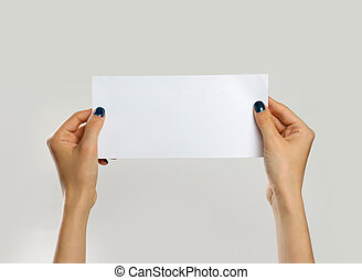 Female hands holding a white sheet of paper. Isolated on gray background. Closeup