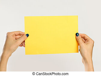 Female hands holding a yellow sheet of paper. Isolated on gray background. Closeup