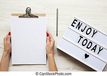 Female hands holding an empty noticepad over white wooden background, top view. 'Enjoy today' word on lightbox. From above, flat-lay, overhead.