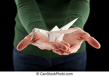 female hands holding an origami crane, focus on bird