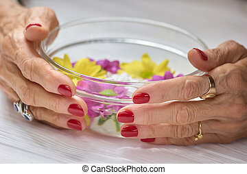 Female hands holding bowl with water. Woman aged hands with...