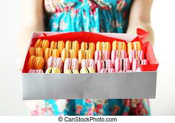 Female hands holding box with colorful french macarons