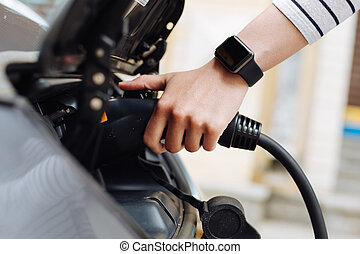 Female hands holding charger for electric car