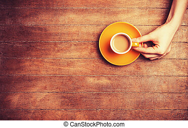 Female hands holding cup of coffee.
