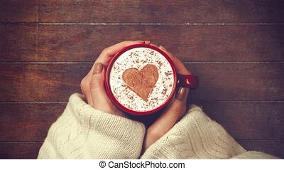 hands holding cup of coffee with heart shape - Female hands...