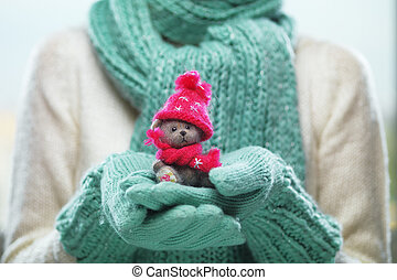 Female hands holding cute teddy bear. Woman hands in teal mittens showing teddy bear gift dresses in pink knitted hat and scarf.