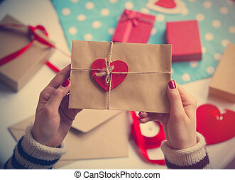 female hands holding envelope with a heart