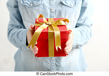 Female hands holding gift box with ribbon