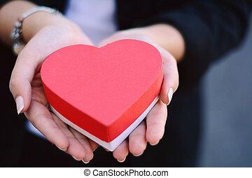 Female hands holding heart shaped gift box.