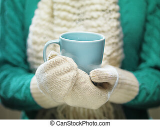 Woman hands in white woolen mittens holding a cozy cup with...