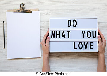 Female hands holding modern board with text 'Do what you love'. Blank noticepad with pencil. White wooden background, top view. From above, flat-lay, overhead.
