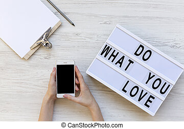 Female hands holding phone with blank screen, top view. Workspace with clipboard, pencil and 'Do what you love' word on modern board. White wooden background. From above, flat-lay, overhead.