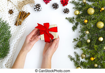 Female hands holding present with red bow on white sparkling background with fir tree,golden balls. Festive backdrop for holidays: Christmas, New Year. Flat lay
