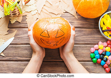 Female hands holding pumpkin with drawing Jack-o-lantern sketch.