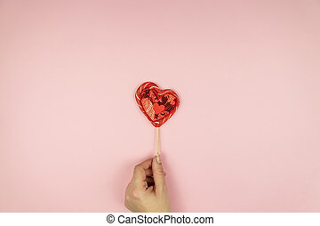Female hands holding red sequin heart on pink background. Creative minimal layout with copy space
