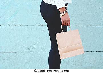 Female hands holding shopping bag outdoors.