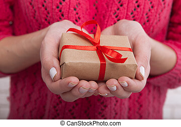 Female hands holding small gift box with ribbon.