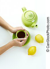 Female hands holding tea cup on table, along with green jug...