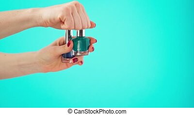 Female hands holding two bottles of nail polish against blue background. High quality 4k footage
