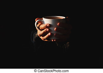 Female hands holding white cup of coffee on black background. Woman warming her hands on mug of hot beverage in the dark. Minimal style. Copy space. Low key