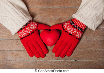 female hands in gloves holding heart shaped toy on the wonderful brown wooden background