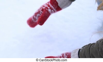 Female hands in knitted mittens making snowball - Close up...