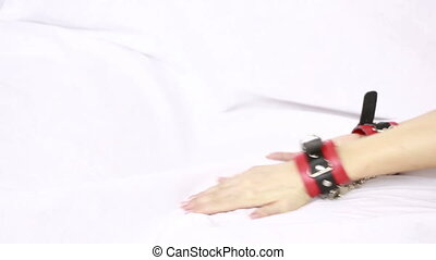 female hands in leather handcuffs. sex toys. grabs the white sheets. red leather