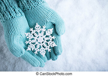Female hands in light teal knitted mittens with sparkling...