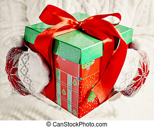 female hands in mittens holding red gift box green